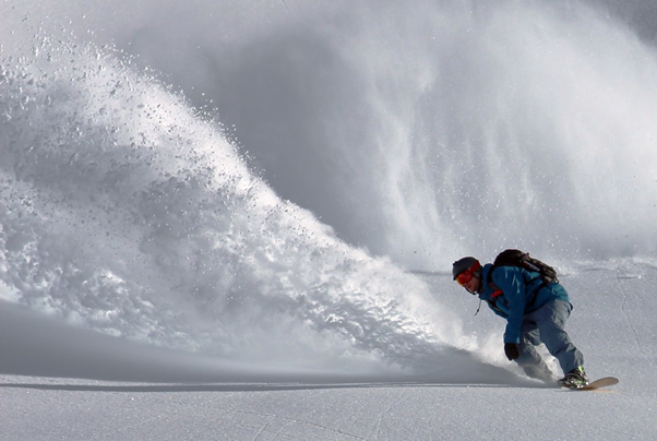 A snowboarder carves down the mountainside