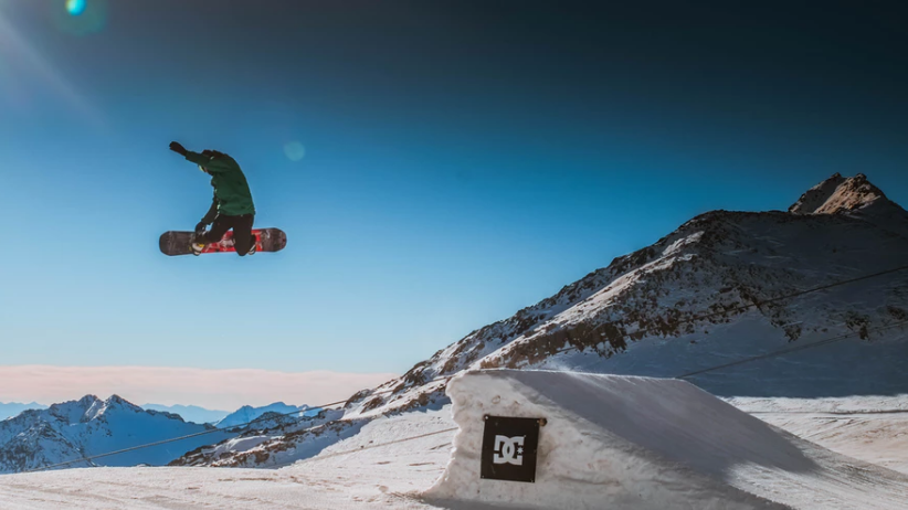 A snowboarder enjoying huge air off a kicker in the Alps